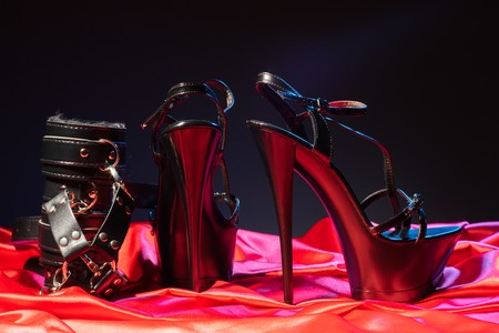 Adult sex games. Kinky lifestyle. Bandages and a pair of black high-heeled shoes on the red linen. Bdsm outfit - Image