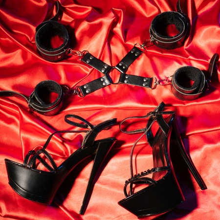 Top view of bdsm outfit. Bondage and a pair of black high-heeled shoes on the red linen. Adult sex games. Kinky lifestyle. -Image
