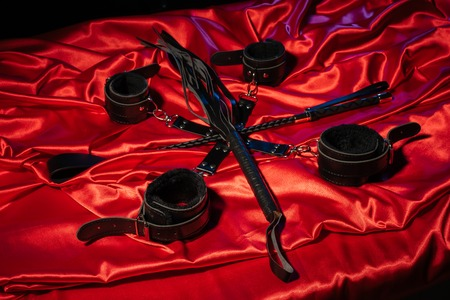 Top view of bdsm outfit. Bondage and whip crossed spank on the red linen. Adult sex games. Kinky lifestyle. - image