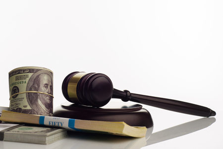 Judges gavel and packs of dollars and euro banknotes on a white background. The concept of growing national debt- image