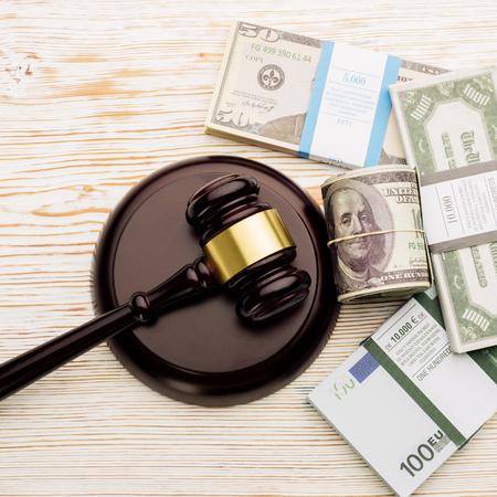 Ansicht von oben Richterhammer und Packungen mit Dollar und Euro-Banknoten auf einem weißen Holztisch. Das Konzept der wachsenden Staatsschulden-Image