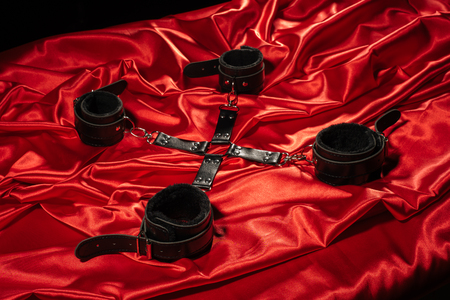 Top view of bdsm outfit. Bondage crossed on the red linen. Adult sex games. Kinky lifestyle. - image