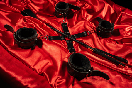 Top view of bdsm outfit. Bondage and spank on the red linen. Adult sex games. Kinky lifestyle. - image