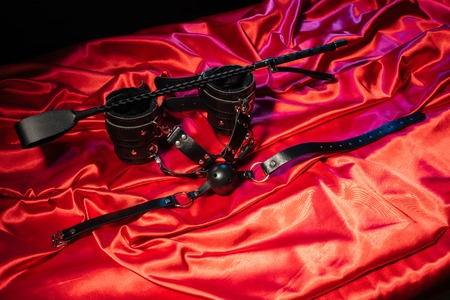 Adult sex games. Kinky lifestyle. Spank, Bondage and gag ball on the red linen. Bdsm outfit Concept - Image Stock Photo