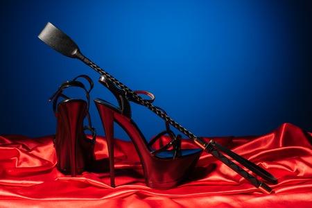 Jeux pour adultes. Mode de vie pervers. Une fessée et une paire de chaussures noires à talons hauts sur le lin rouge près du mur bleu. Tenue bdsm - Image Banque d'images
