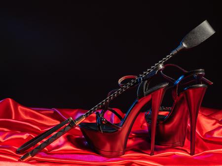 Volwassen spellen. Kinky levensstijl. Spank en een paar zwarte schoenen met hoge hakken op het rode linnen. Bdsm-outfit - Afbeelding