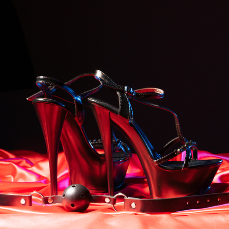 Adult sex games. Kinky lifestyle. Gag ball and a pair of black high-heeled shoes on the red linen. Bdsm outfit - Image Stockfoto