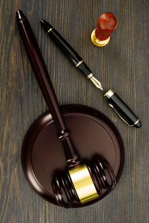 Judge's gavel, fountain pen and a stamp on an old wooden table - Image