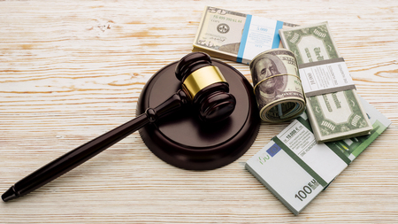 Top view Judges gavel and packs of dollars and euro banknotes on a white wooden table.The concept of growing national debt- image