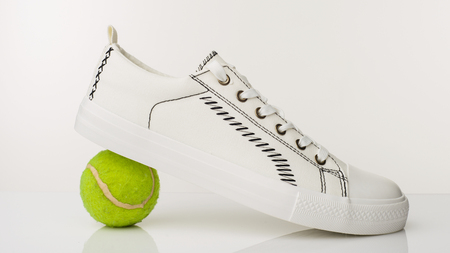 Fashionable white walking shoes with tennis ball on a white background. - image Standard-Bild