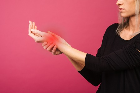 Female holding hand to spot of wrist pain. Concept photo with Color Enhanced skin with read spot indicating location of the pain. Stock Photo