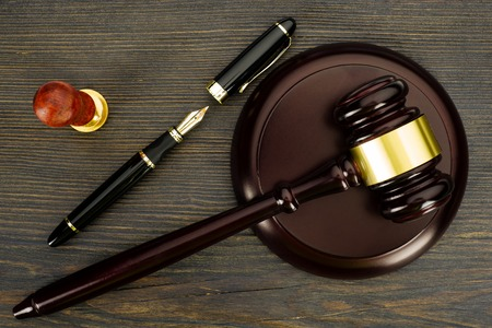 Judge's gavel, fountain pen and a stamp on an old wooden table - Image Stock Photo