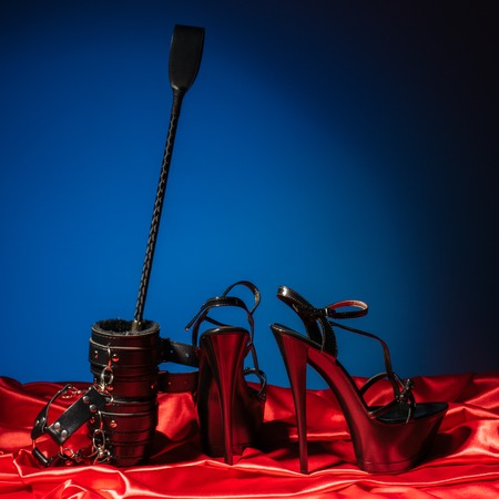 Adult sex games. Kinky lifestyle. Spank and a pair of black high-heeled shoes on the red linen near blue wall. Bdsm outfit - Image