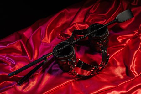 Adult games. Kinky lifestyle. Spank and Bondage on the red linen. Bdsm outfit - Image