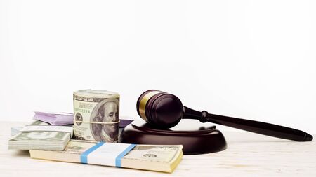 Judges gavel and packs of dollars and euro banknotes on a white wooden table. The concept of growing national debt- image