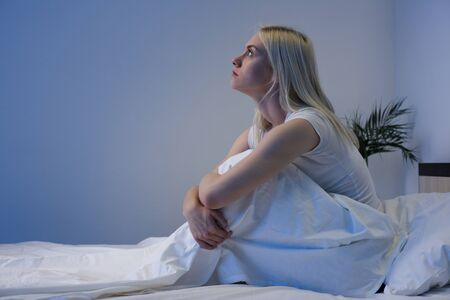 Sad depressed woman sitting in her bed late at night, she is pensive and suffering from insomnia - Image