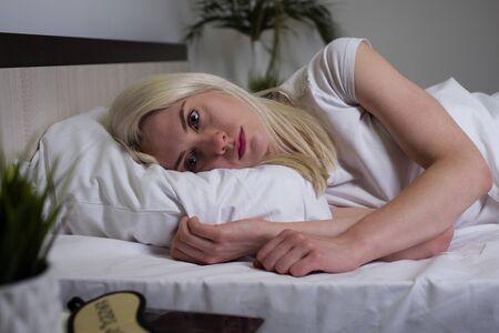 jonge mooie vrouw thuis slaapkamer die 's avonds laat in bed ligt en probeert te slapen met slapeloosheid slaapstoornis of bang voor nachtmerries die er verdrietig, bezorgd en gestrest uitziet - afbeelding