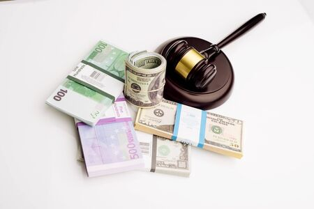 Top view Judge's gavel and packs of dollars and euro banknotes on a white background. The concept of growing national debt- image
