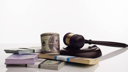 Judge's gavel and packs of dollars and euro banknotes on a white background. The concept of growing national debt- image Stock Photo - 125480162