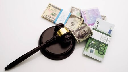 Top view Judges gavel and packs of dollars and euro banknotes on a white background. The concept of growing national debt- image