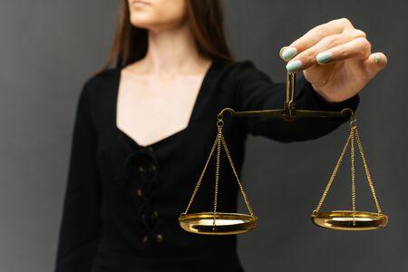 Ernste Frau, die die Gerechtigkeitsskala auf dunklem Hintergrund hält - Bild Standard-Bild