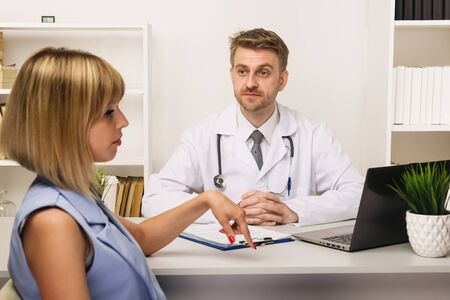 Young woman on a consultation with a male surgeon or therapist in his office. Selective focus on the doctor. Standard-Bild
