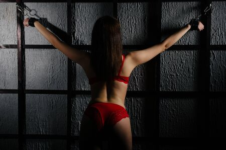 BDSM outfit for adult sex games. A young woman chained to the bars with handcuffs with bondage awaiting punishment. - Image