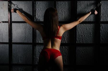 Tenue BDSM pour jeux pour adultes. Une jeune femme enchaînée aux barreaux avec des menottes en attente de punition. - Image
