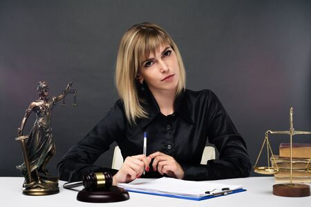 A young fair woman judge works in her office. - image Standard-Bild