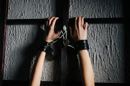 BDSM outfit for adult games. Close-up of female hands handcuffed bondsge to the bars - image