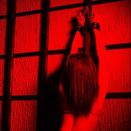 BDSM outfit for adult sex games. A young woman in red light chained to the bars with handcuffs with bondage awaiting punishment.
