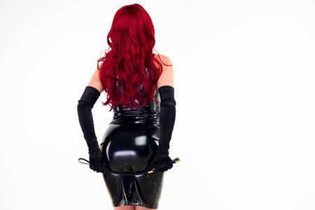 Die rothaarige leidenschaftliche Dame in einem schwarzen Latexkleid steht mit dem Rücken und hält den Hintern mit einem Prügel auf weißem Hintergrund