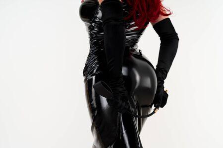 La donna appassionata dai capelli rossi in un vestito di lattice nero è in piedi con la schiena che tiene il didietro con una frusta su uno sfondo bianco