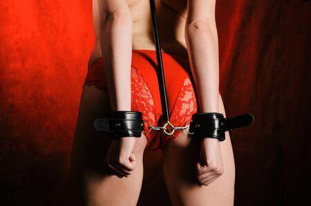 Traje BDSM para juegos de adultos. Una mujer joven de pie con la espalda encadenada a los grilletes esposados esperando el castigo. Fondo rojo y ropa interior lencería