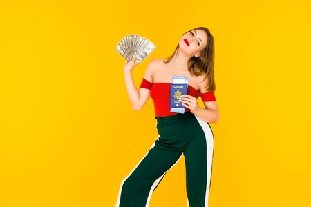 A young woman holds a money and passport with airline tickets. . Stylish girl on in a red blouse and green pants on a yellow background. - image