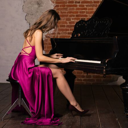 Young elegant woman in evening dress with naked back playing retro piano