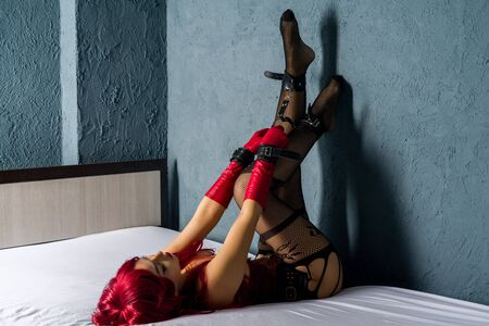 Slave red-haired woman in a corset and red leather gloves seductively posing lying back on the bed and legs up. Hands and feet shackled bondage cross.