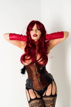 Redhead slave woman in a red wig, corset and leather gloves posing on a white background. Attached to the naked chest clamps with feathers 免版税图像