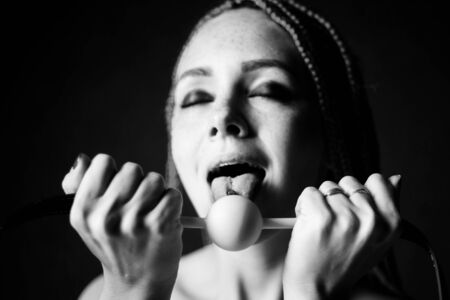 BDSM outfit for adult sex games. A young woman licks gag ball - Black and white image