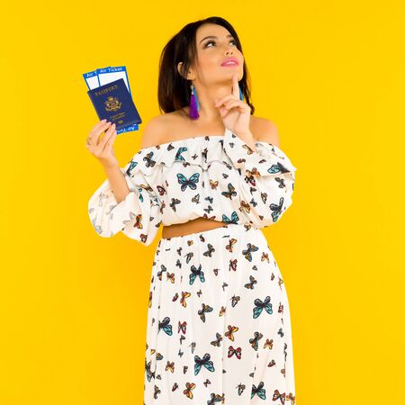 A cute Asian woman in a silk dress with butterflies is holding a passport and air tickets on a yellow background. Travel concept. Reklamní fotografie