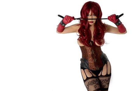 Dominante Frau in einem roten Perückenkorsett und Lederhandschuhen, die auf einem weißen Hintergrund posieren. Herrin hält zur Bestrafung eine Peitsche in den Händen einen Flip Flop