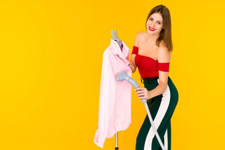 Young woman steaming pink shirt at dry-cleaner's on yellow background 写真素材