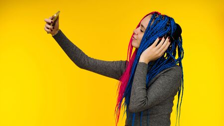 Happy cheerful woman with senegalese braids and freckles wearing wireless headphones listening to music from smartphone studio shot isolated on yellow background Stock Photo