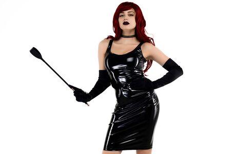 Rothaarige leidenschaftliche Dame in einem schwarzen Latexkleid posiert mit einer Peitsche in den Händen auf weißem Hintergrund