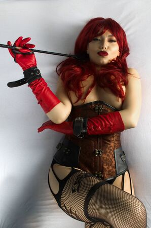 Red-haired woman in a red wig, corset and leather gloves posing lying on a bed holding a stick in the hands of a whip. Bdsm outfit