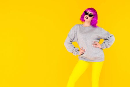 Fashion girl portrait on yellow background. Crazy style young woman in pink wig - image 스톡 콘텐츠