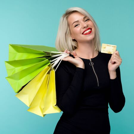 Image of a beautiful happy young blonde woman posing isolated over blue wall background holding shopping bags. Black Friday Holiday Concept. Sale Imagens
