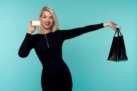 Image of a beautiful happy young blonde woman posing isolated over blue wall background holding shopping bags. Black Friday Holiday Concept. Sale Imagens - 128571689