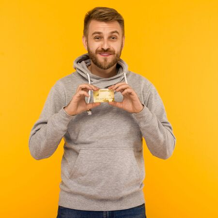 Attractive man in a gray hoodie holds a credit card in his hands on a yellow background - image Stock Photo