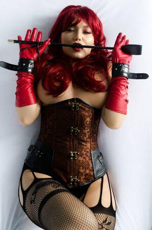 Mujer pelirroja con una peluca roja, corsé y guantes de cuero posando acostada en una cama sosteniendo un palo en las manos de un látigo. Traje bdsm Foto de archivo
